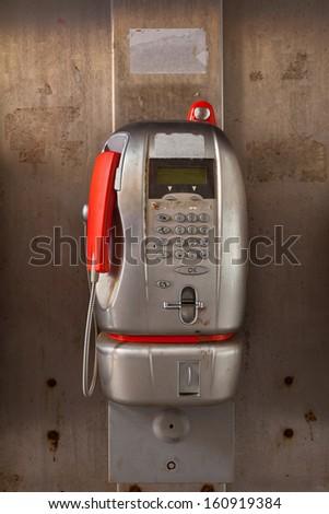 Aluminium public telephone with a red handset. - stock photo