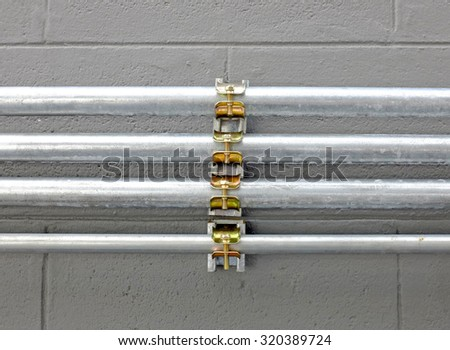 aluminium wire pipe at cement wall - stock photo