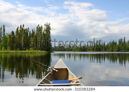 Aluminum canoe with fishing gear heading out on a northern Minnesota lake - stock photo
