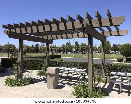 Aluminum dining table under light shading pergola - stock photo