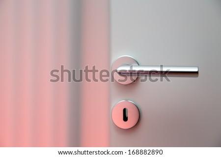 Aluminum door knob (door handle) on the white door - stock photo