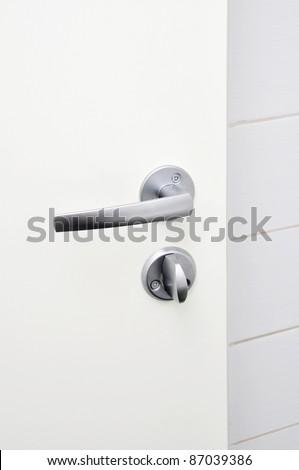 Aluminum door knob on the white door - stock photo