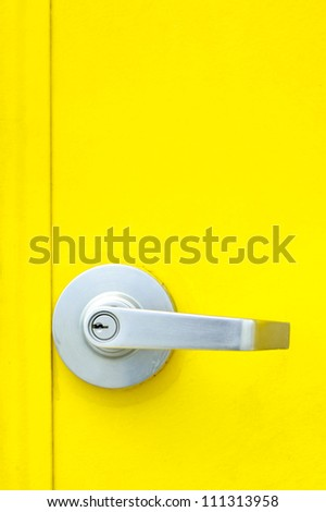 Aluminum door knob on the yellow door.