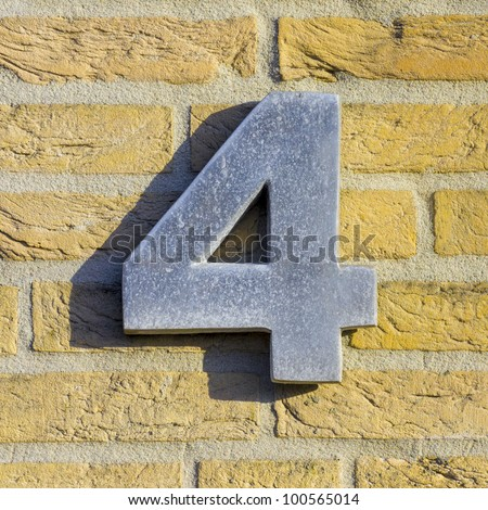 aluminum house number 4 on a yellow brick wall - stock photo