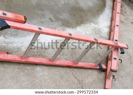 aluminum ladder red fallen to the floor - stock photo