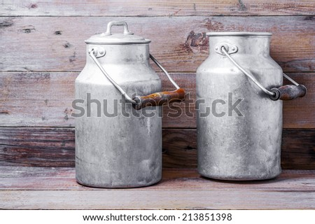 Aluminum old milk cans on a wooden background - stock photo