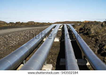 Aluminum pipes for transporting energy in rugged landscape - stock photo