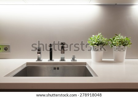 Aluminum sink in kitchen with flowers on wheat - stock photo