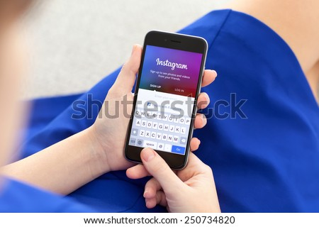 Alushta, Russia - December 3, 2014: Woman holding a iPhone 6 Space Gray with social networking service Instagram on the screen. iPhone 6 was created and developed by the Apple inc. - stock photo