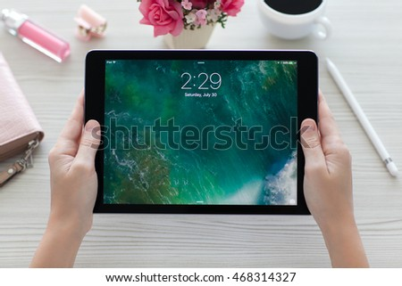 Alushta, Russia - July 30, 2016: Woman holding in the hand a iPad Pro Space Gray with wallpaper IOS 10. iPad Pro was created and developed by the Apple inc.