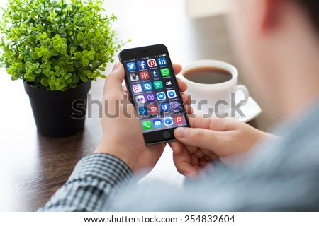 Alushta, Russia - November 20, 2014: A set of programs from famous brands of social networking on the phone iPhone 6 in man hands. iPhone 6 was created and developed by the Apple inc.