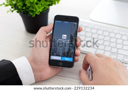 Alushta, Russia - November 3, 2014: Businessman holding a iPhone 6 Space Gray with social network service LinkedIn on the screen. iPhone 6 was created and developed by the Apple inc. - stock photo