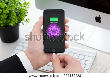 Alushta, Russia - November 3, 2014: Man holding a iPhone 6 Space Gray with battery icon on the screen. iPhone 6 was created and developed by the Apple inc. - stock photo