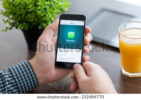 Alushta, Russia - November 21, 2014: Man holding a iPhone 6 Space Gray with social Internet service WhatsApp on the screen. iPhone 6 was created and developed by the Apple inc. - stock photo