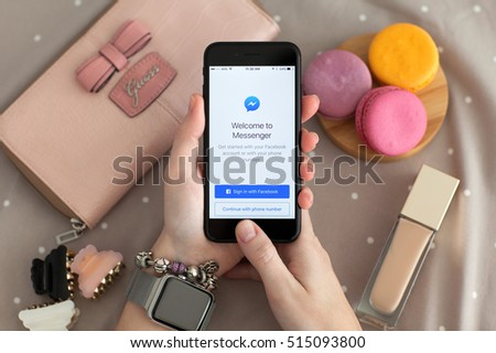 Alushta, Russia - November 11, 2016: Woman hand with Apple Watch holding iPhone 7 Jet Black with social networking service Facebook Messenger on the screen.