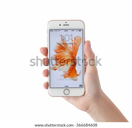 Alushta, Russia - November 12, 2015:  Woman unlock iPhone6S Rose Gold in the hand on the white background. iPhone 6S Rose Gold was created and developed by the Apple inc. - stock photo