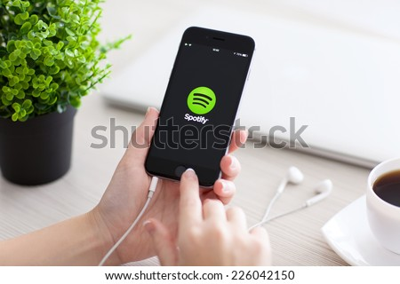 Alushta, Russia - October 24, 2014: Girl holding a iPhone 6 Space Gray with music service Spotify on the screen. iPhone 6 was created and developed by the Apple inc. - stock photo