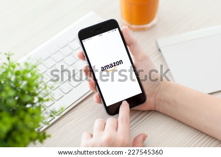 Alushta, Russia - October 25, 2014: Girl holding a iPhone 6 Space Gray with service Amazon on the screen. iPhone 6 was created and developed by the Apple inc. - stock photo