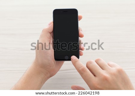 Alushta, Russia - October 23, 2014: Man switch on the new iPhone 6 Space Gray holding it over the table. iPhone 6 was created and developed by the Apple inc. - stock photo