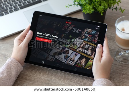 Alushta, Russia - October 9, 2016: Woman holding iPad Pro with entertainment company Netflix provides streaming media and video on the screen. iPad Pro 9.7 was created and developed by the Apple inc.
