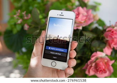 Alushta, Russia - September 30, 2014: Woman holding a iPhone 5 S with social networking service Instagram on the screen. iPhone was created and developed by the Apple inc. - stock photo