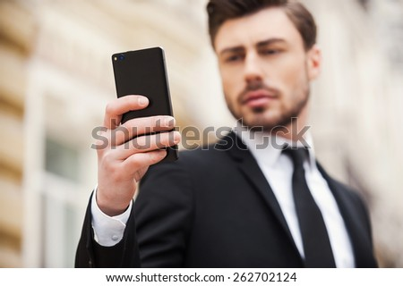 Always connected. Confident young man in formalwear holding mobile phone while standing outdoors  - stock photo
