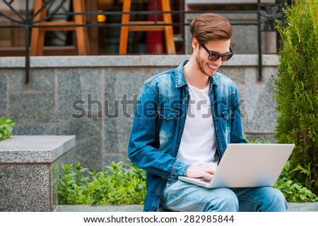 Always connected. Smiling young man working on laptop while sitting outdoors - stock photo