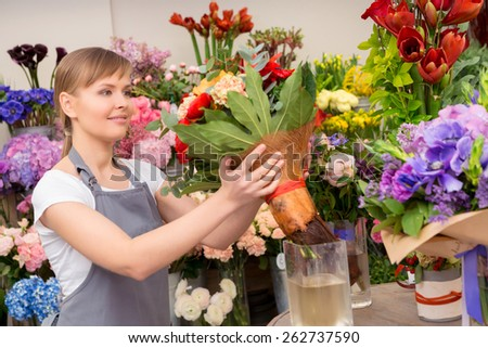 Always fresh and beautiful. Attractive young florist putting a bouquet into the water pot standing on a counter - stock photo