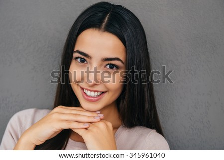 Always in good mood. Beautiful young woman holding hands on chin and smiling while standing against grey background - stock photo