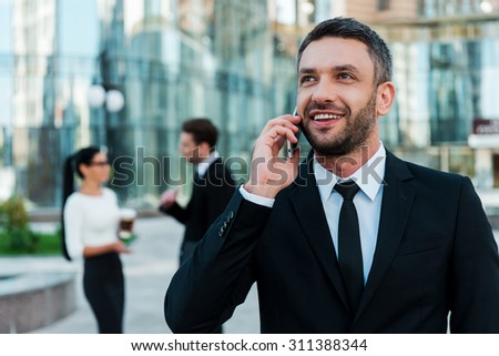 Always in touch with his clients. Cheerful young businessman talking on the phone and looking away while two his colleagues talking to each other in the background - stock photo