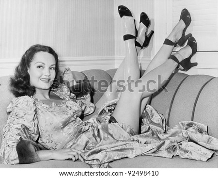 Always nice to have a spare, a young woman sits on her sofa with four legs - stock photo