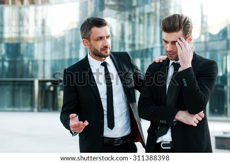 Always ready to help his friend. Frustrated young businessman touching his forehead while his colleague consoling him  - stock photo