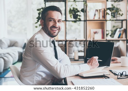 Always ready to help you. Confident mature man in shirt and tie looking at camera and smiling while sitting at his working place in office  - stock photo