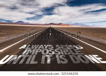 Always Seems Impossible Until it is Done written on desert road - stock photo