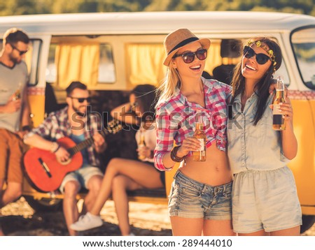 Always together and never apart. Two cheerful young women holding bottles of beer while their friends sitting at the background in retro minivan  - stock photo