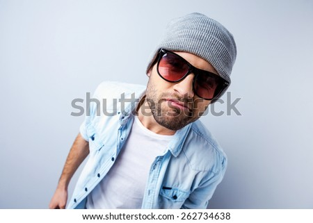 Am I cool enough? Top view of handsome young man in hat and sunglasses looking at camera and grimacing while standing against grey background - stock photo