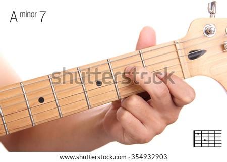 Am7 - minor seventh keys guitar tutorial series. Closeup of hand playing A minor seventh chord on guitar, isolated on white background