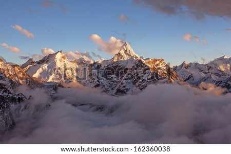 Ama Dablam peak (6856 m) above the clouds in the soft evening light. Canon 5D MkII. - stock photo