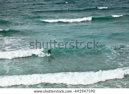 AMADO, CARRAPATEIRA, SAGRES, ALGARVE, PORTUGAL - September 28, 2012: Surfer on a board on the crest of the waves of the Atlantic Ocean near Amado beach, Carrapateira; Sagres; Algarve, Portugal - stock photo