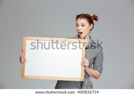 Amamzed cute young woman holding and looking at blank whiteboard over grey background - stock photo