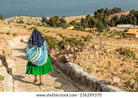 AMANTANI ISLAND, PUNO, PERU:  Woman with traditional dress down the hike in Amantani island. - stock photo