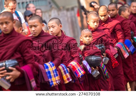 AMARAPURA, MYANMAR - MARCH 10 : Young Buddhist monks waiting in line for lunch during an Alms Ceremony at the Maha Gandayon Monastery on March 10,2015,Mandalay Division,Central of Myanmar. - stock photo