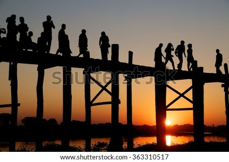 AMARAPURA, NEAR MANDALAY, MYANMAR - 17 NOVEMBER 2014.  Tourists on the U-Bein Bridge at sunset. The bridge measures 1.2 kilometers and is thought to be the longest teak bridge in the world.