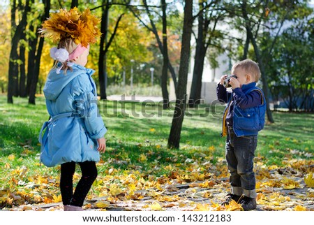 Amateur small photographer - a little boy practices photographing his sister wearing a crown of yellow autumn leaves with a retro slr camera