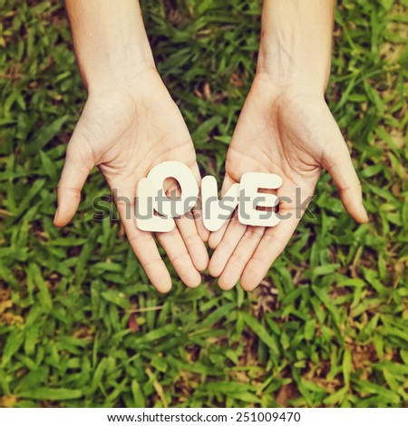 "amateur style photo of word love in two hands (""instagram"" filter is applied) - stock photo"