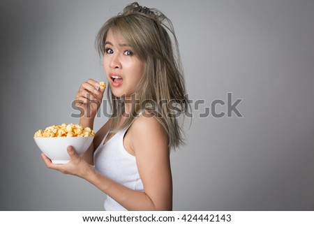 Amazed asian woman with popcorn