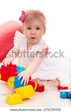 Amazed baby girl playing with colorful bricks toys - stock photo