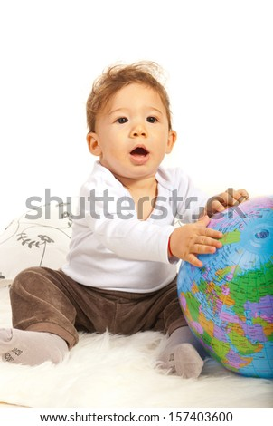 Amazed baby with world globe sitting on fur blanket - stock photo