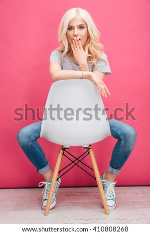 Amazed blonde woman sitting on the chair over pink background - stock photo