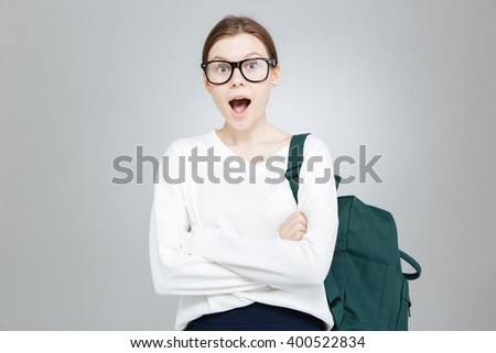 Amazed charming teenage girl in glasses with backpack standing with opened mouth